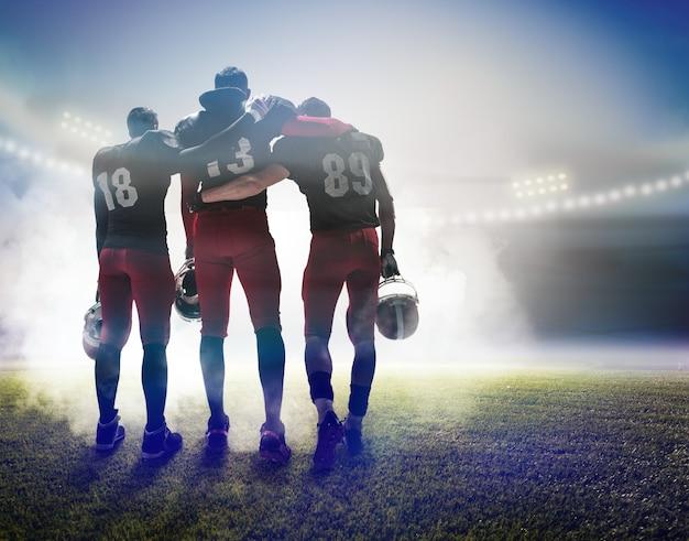 スタジアムの背景にアメリカンフットボール選手として3人の白人フィットネス男性の背面図
