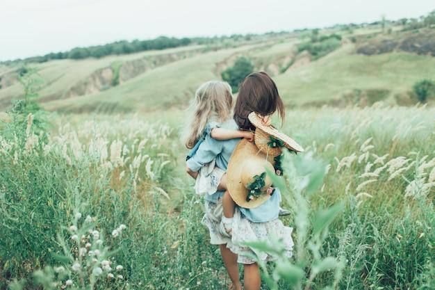 緑の芝生の上の若い母と娘の背面図。