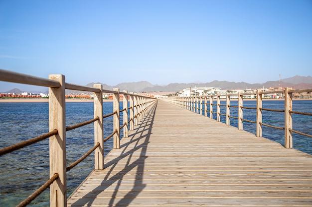 На заднем плане - красивый длинный деревянный пирс среди океана и гор.