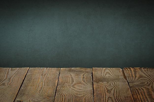 배경은 빈 나무 판과 조명과 비네팅이있는 질감이있는 회 반죽 벽입니다.