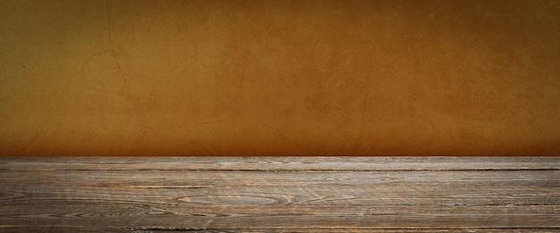 배경은 빈 나무 판자와 질감이 있는 회반죽 벽입니다