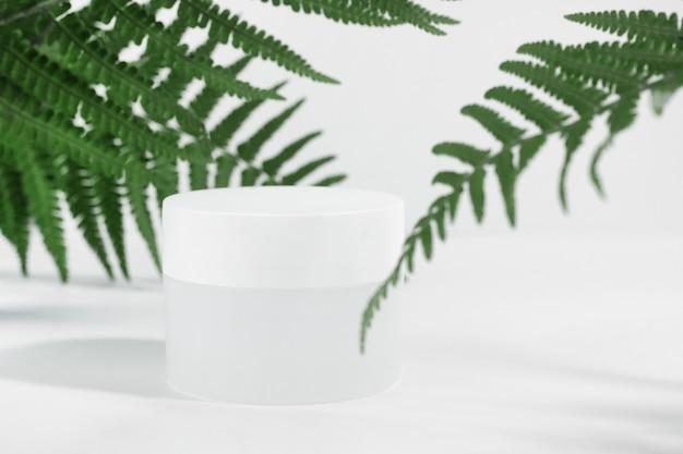 背景は化粧品です。熱帯のシダの葉とハードシャドウと白い背景で隔離の白い容器に顔の保湿剤の白い瓶。美容またはスキンケアの概念。コピースペース