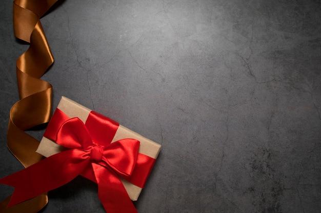 Фон с местом для текста в коробке темного цвета с подарком и красной лентой и декоративной золотой лентой. копировать пространство.