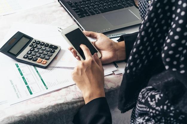 携帯電話とラップトップ、電卓、レポートに取り組んでいるビジネスのイスラム教徒の女性の裏側。