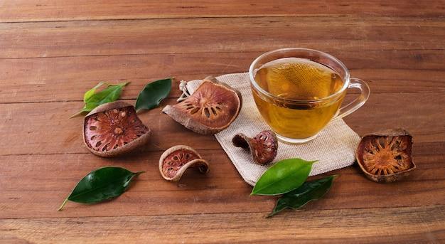 Фруктовый сок bael в стакане и сушеные фрукты bael, помещенные на деревянный стол.