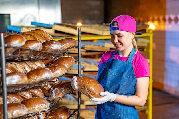 パン屋は、パン屋のパンと一緒に棚の背景に熱いパンを持っています。工業用パンの生産。