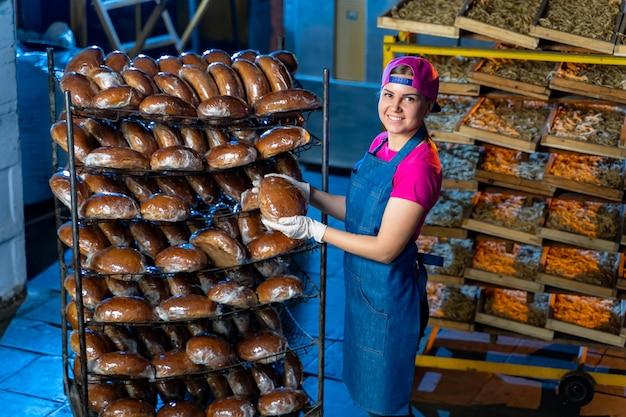 Пекарь держит горячий хлеб на фоне полок с хлебом в пекарне. промышленное производство хлеба