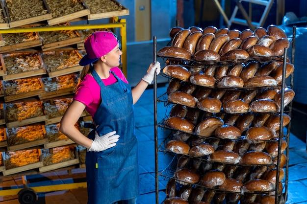 パン屋は、パン屋のパンと一緒に棚の背景に熱いパンを持っています。工業用パンの生産