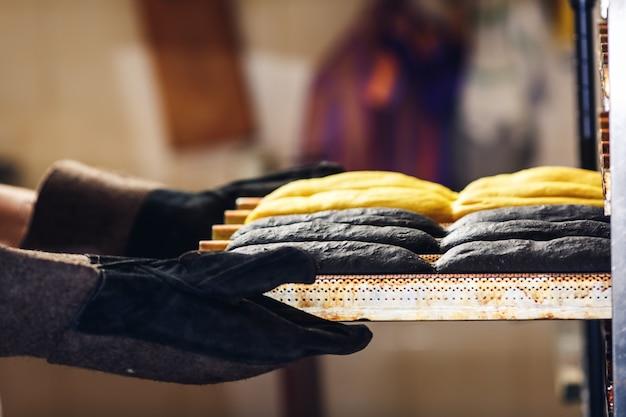 パン屋は、ホットドッグ用の黄色と黒のパンが入ったトレイを持っています。