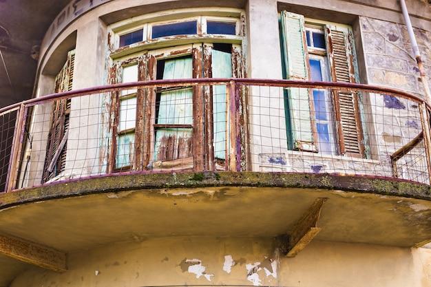 廃墟のビルのベランダ。バルコニー付きのほとんど台無しにされた古い家の壁の詳細。