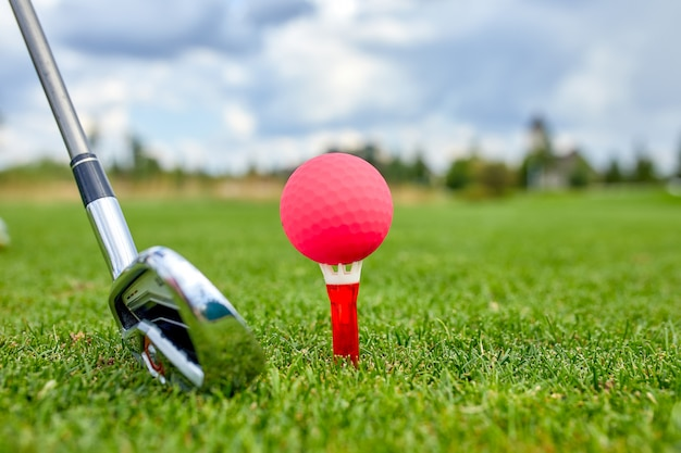 골프 코스의 구멍에있는 공. 골프 개념. 히트하기 전에 골프 클럽 옆에 녹색 잔디에 골프 공의 근접 촬영.