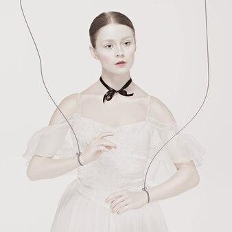 흰색 표면 위에 춤추는 꼭두각시와 같은 발레 댄서