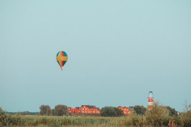 気球は夕方の光の中で赤い家と灯台の村の近くを飛ぶ