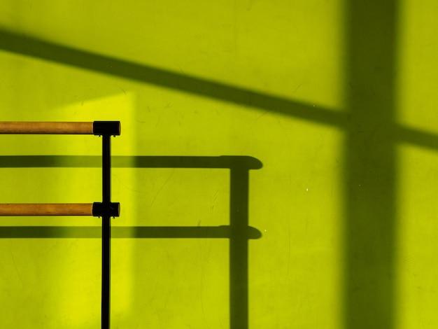緑の壁のあるスポーツホールの振り付け用バー。
