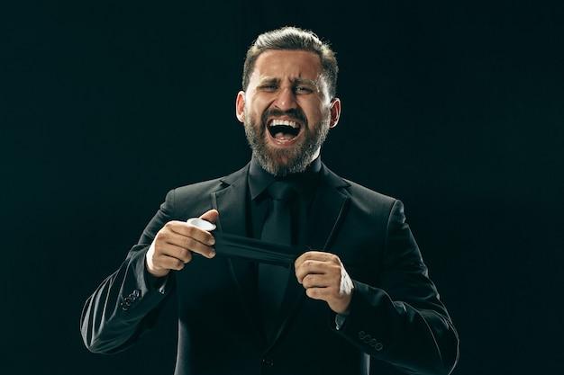 양복 입은 남자. 검은 스튜디오 배경에 세련 된 비즈니스 사람입니다. 아름다운 남성 초상화. 감정적 인 젊은이