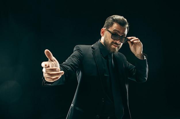 スーツを着たバードマン。黒のスタジオでスタイリッシュなビジネスの男性