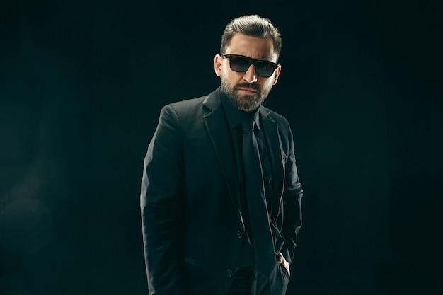 Мужчина в штанге в костюме. стильный деловой человек на черной студии