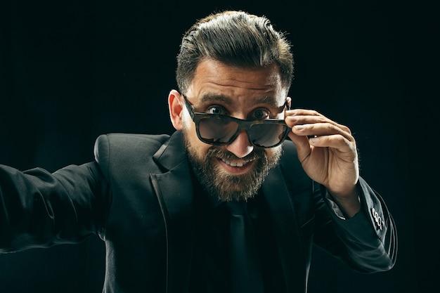 スーツを着たバード男。黒のスタジオでスタイリッシュなビジネスマン