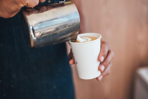 바리스타는 깡통의 우유를 종이 일회용 컵에 담긴 커피에 붓습니다.