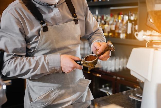バリスタは、モダンなコーヒーショップのクローズアップでおいしいコーヒーを準備します。