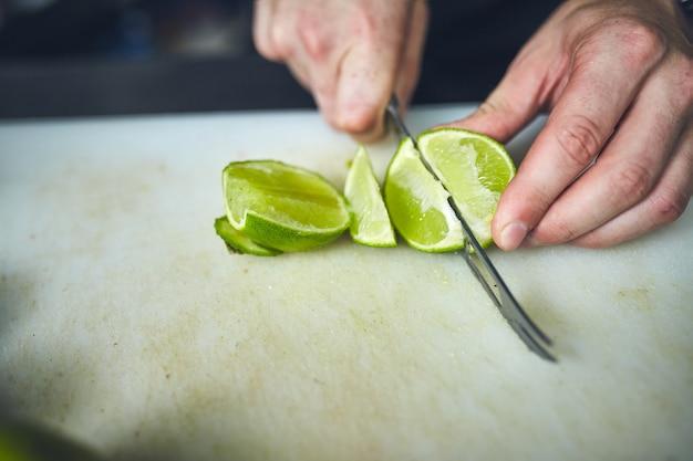 Бармен режет лимон на разделочной доске