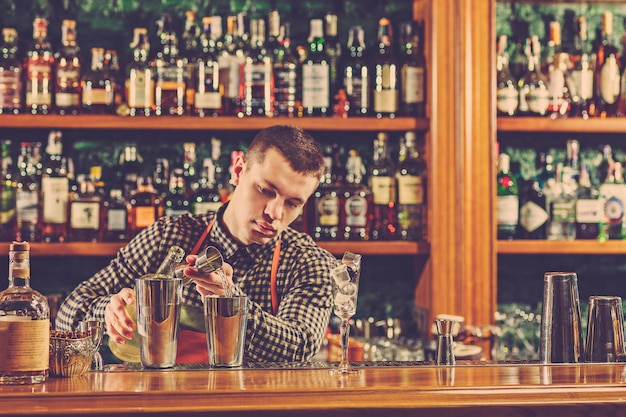 Бармен готовит алкогольный коктейль за барной стойкой на барной стойке
