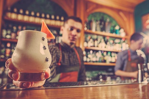 バースペースのバーカウンターでアルコールカクテルを提供するバーテンダー