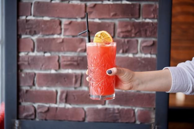 バーテンダーは、赤レンガの壁の背景にオレンジで飾られたガラスで新鮮なおいしい赤い夏のカクテルを保持しています。テキスト用のスペース。