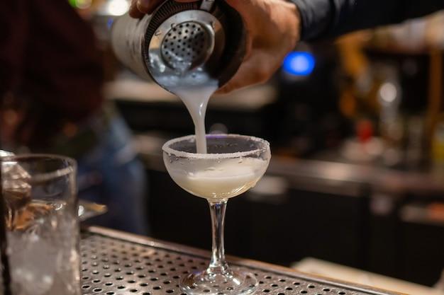 バーテンダーがバーでカクテルを作り、シェーカーをグラスに注ぐ