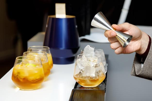 バーテンダーはカクテルを作ります。バーメンは鋼の測定ガラスからアルコールを注ぎます。