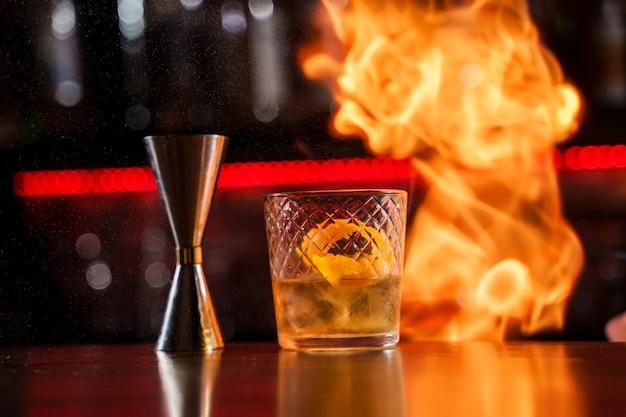 Бармен разводит пламя над коктейлем с апельсиновой коркой крупным планом.