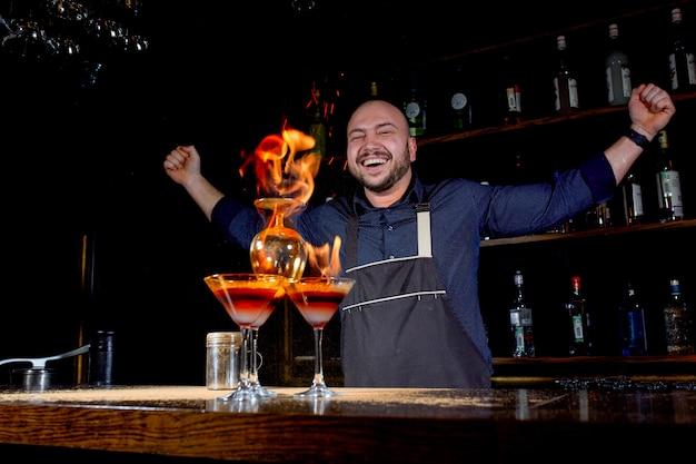 バーテンダーが熱いアルコールカクテルを作り、バーに火を付ける