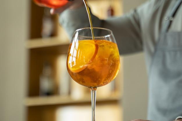 Бармен готовит коктейль, наливает в бокал апельсиновый сироп.