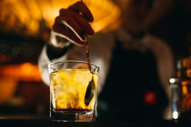 バーテンダーはグラスに氷を入れたウイスキーをスプーン一杯かき混ぜます
