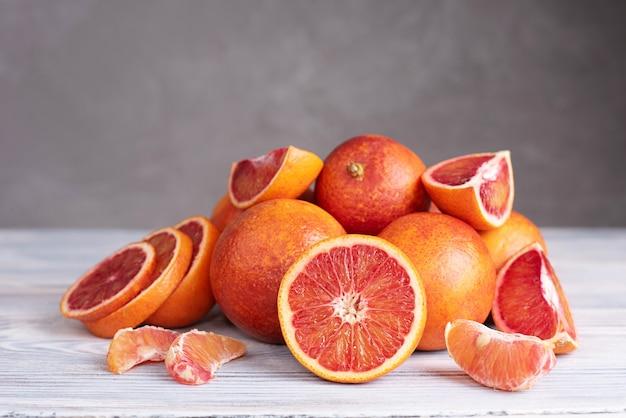 Партия свежего сочного кровавого апельсина на сером