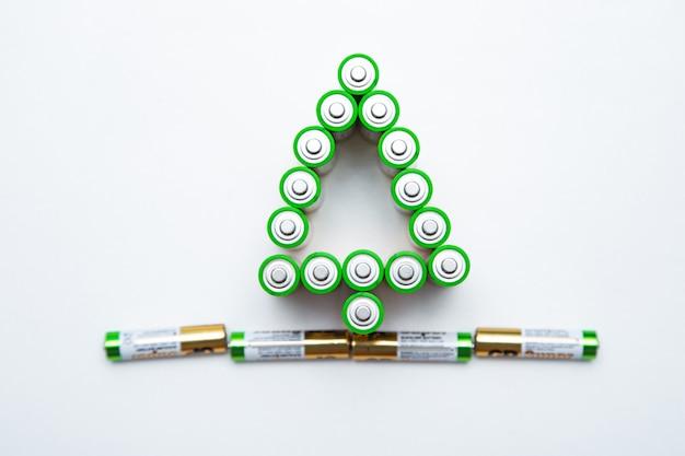 電池は白い背景の上のクリスマスツリーの形をしています。上面図、フラットレイ、コピースペース、分離。高品質の写真