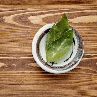 Лавровые листья в керамической миске на ветхом деревянном.