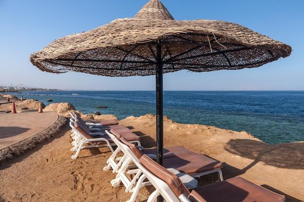 エジプトのシャルムエルシェイクにある高級ホテルのビーチ。青い空を背景の傘