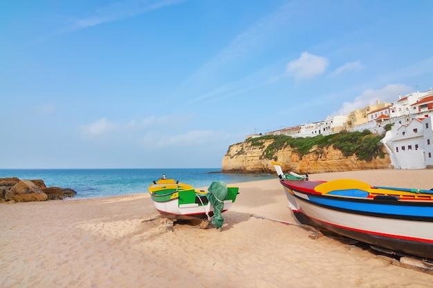 Пляж в поселке карвоейру с рыбацкими лодками на переднем плане. португалия, лето.