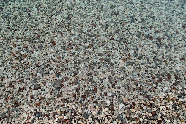 해변은 자갈, 해변, 물 속의 작은 색깔의 자갈로 이루어져 있습니다. 배경, 복사 공간입니다.