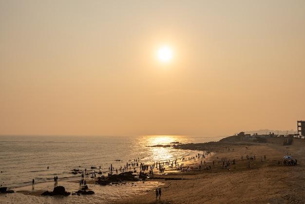 석양 아래 해변은 황금색입니다.