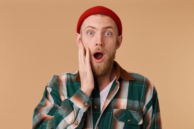 Бородатый парень смотрит на что-то невероятное, невообразимое уникальное, широко открытыми глазами придерживая руку возле щеки.