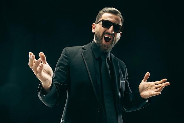 Бородатый мужчина в костюме в черной студии
