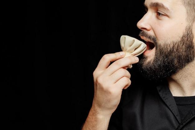 Бородатый эмоционально ест хинкали. национальное грузинское блюдо хинкали.
