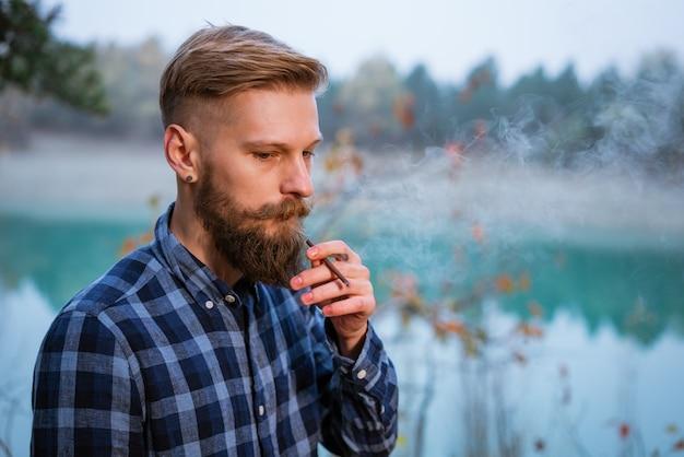 수염 난 남자는 담배 니코틴 중독과 나쁜 격자 무늬 셔츠에 잘 생긴 세련된 남자를 피우다