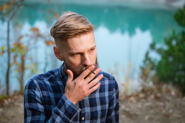 수염 난 남자는 담배 니코틴 중독과 나쁜 격자 무늬 셔츠에 잘 생긴 세련된 남자를 피우고 ...