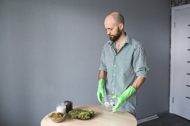 Бородатый мужчина пересаживает суккуленты и мох в стеклянную вазу. флорариум с суккулентами, пересадка растений, концепция дня земли.