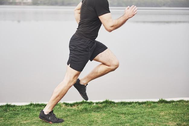 Бородатый молодой человек занимается спортом на открытом воздухе