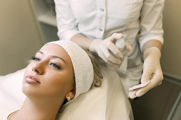 Косметолог наносит очищающее средство на ватный тампон