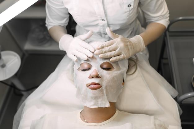Косметолог накладывает косметическую маску на лицо пациентки девушки
